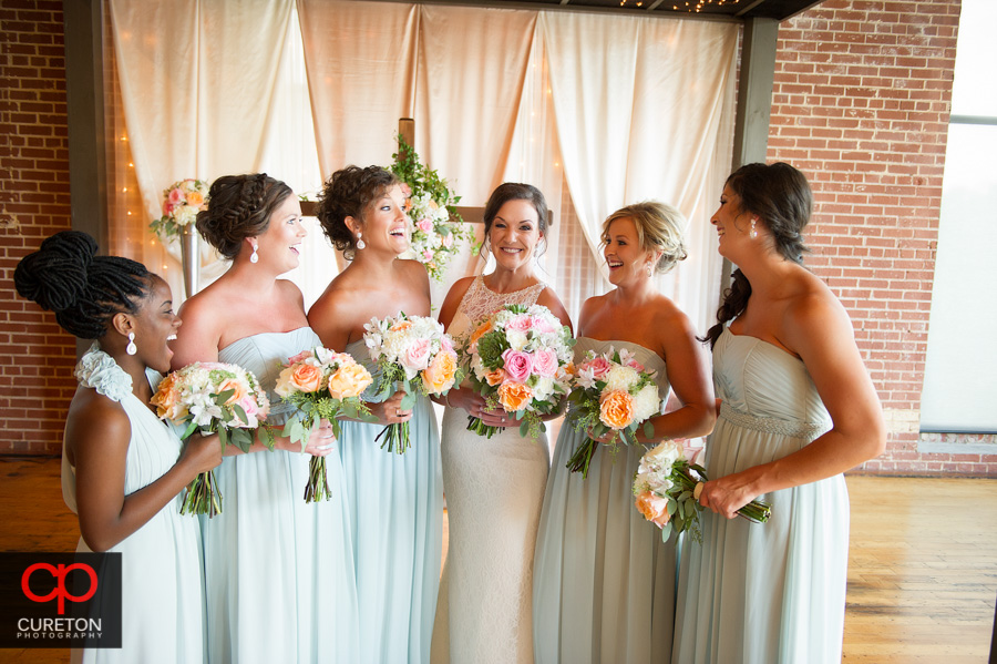 The bride and bridesmaids laughing having a good time.