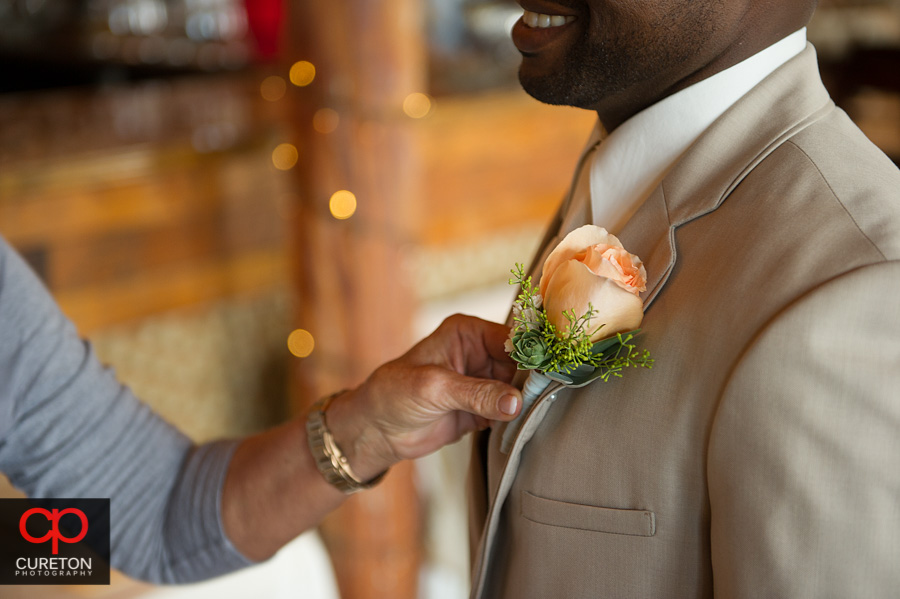 The groom getting his boutonnière pinned.