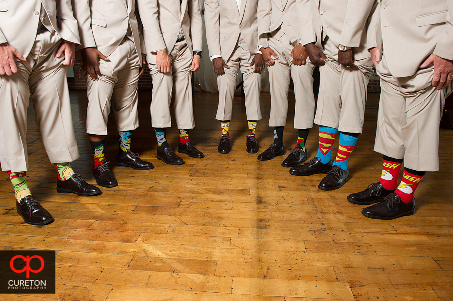 The groomsmen shoeing off their super hero socks.