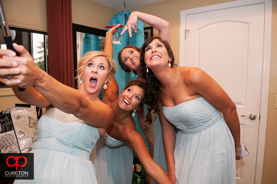 Bridesmaids using a selfie stick.
