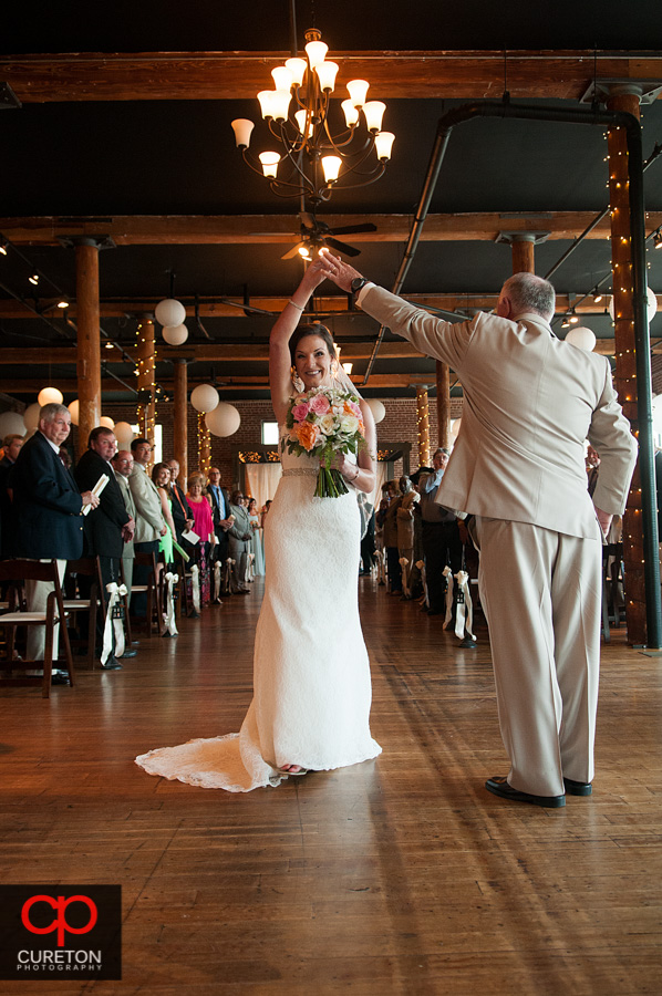Bride and her father twirl going down the aisle at The Loom in Simpsonville,SC..
