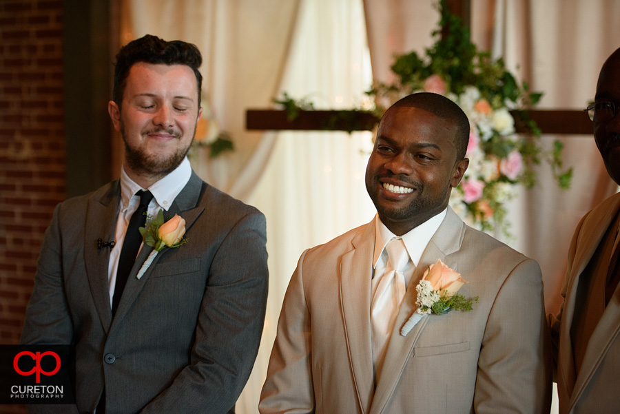 The groom smiling when he first sees his bride.