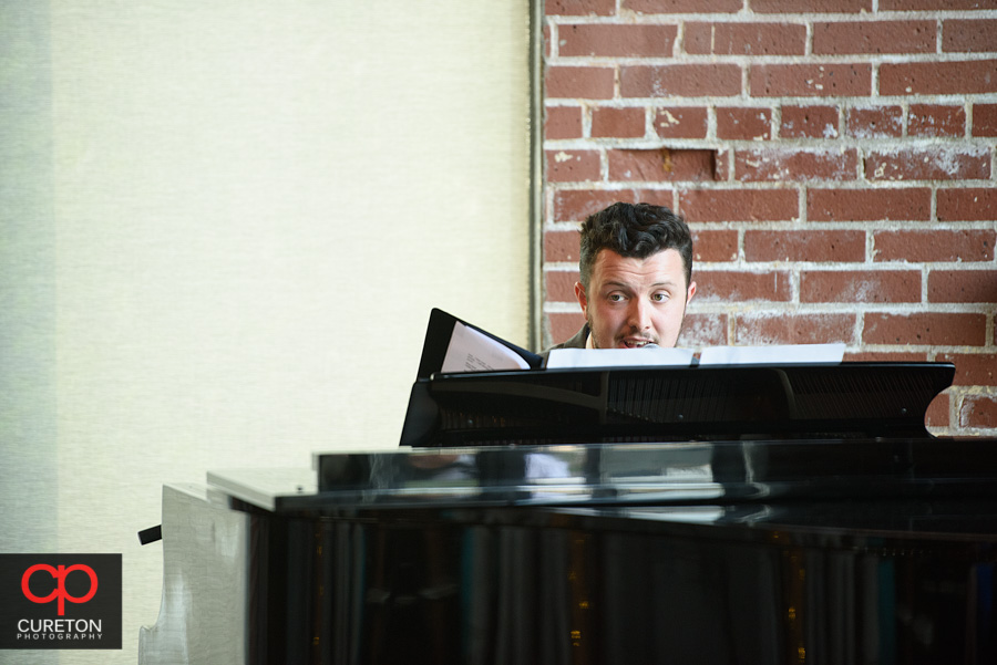 The minister plays a song on the piano.