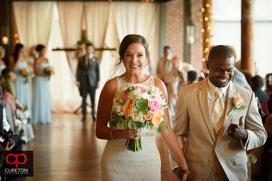 Bride smiling while walking back down the aisle.