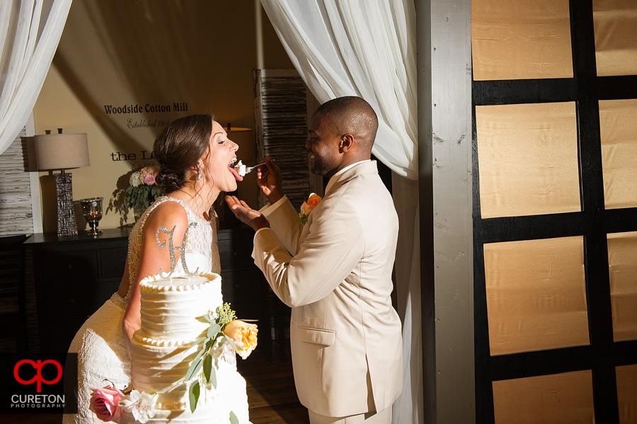 The groom feeding cake to the bride.