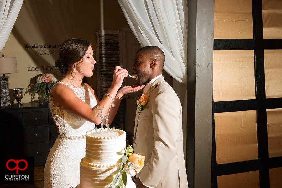 The bride feeding cake to the groom.