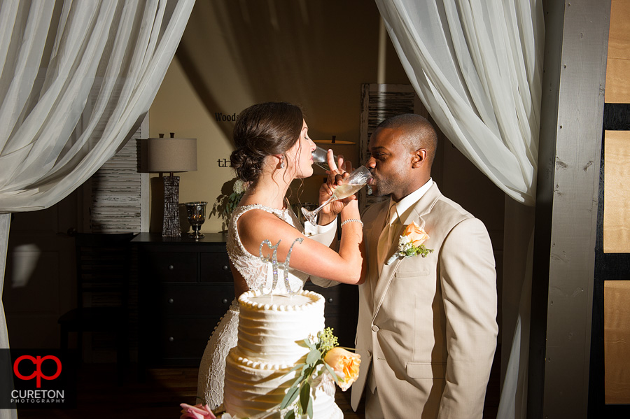 The bride and groom share a glass of champagne.