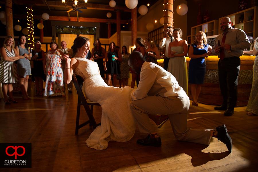 Groom taking off bride's garter.