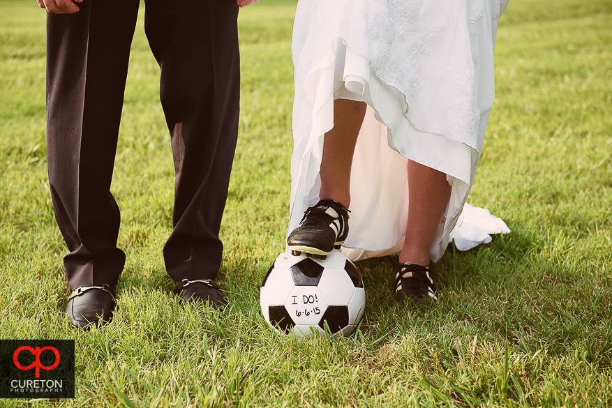 Bride and groom posing with a soccer ball with their wedding date on it.