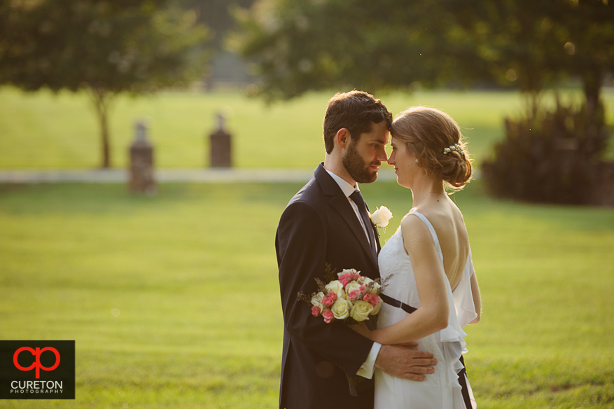 Bride and groom standing face-to-face in a pasture at their Timberock at Hopkins Farm wedding in Simpsonville,SC.