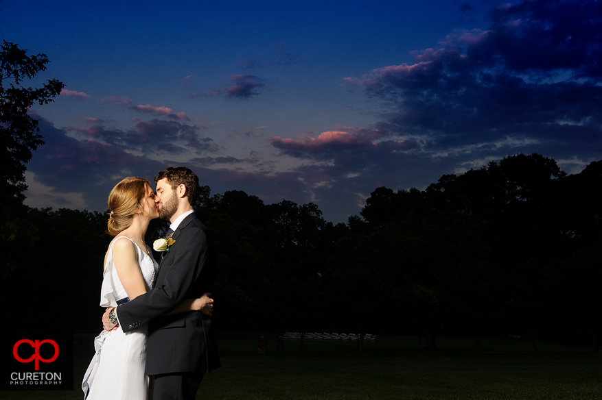 Bride and Groom kissing at sunset after their Timberock at Hopkins Farm wedding in Simpsonville,SC.