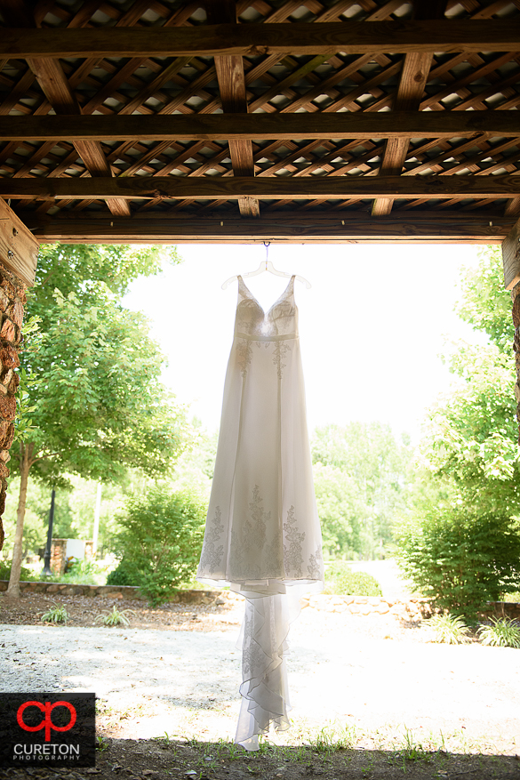 Brides dress hanging up at the rustic farmhouse.