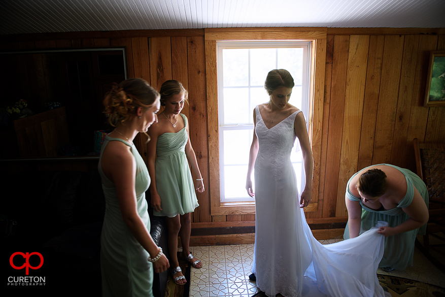 The bridesmaids helping the bride get into her dress.