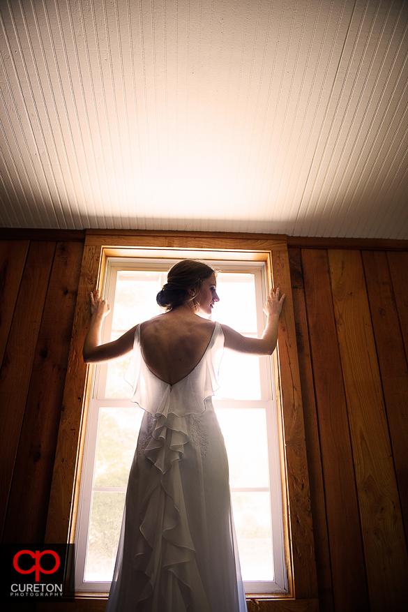 The bride posing in front of sun lit window.