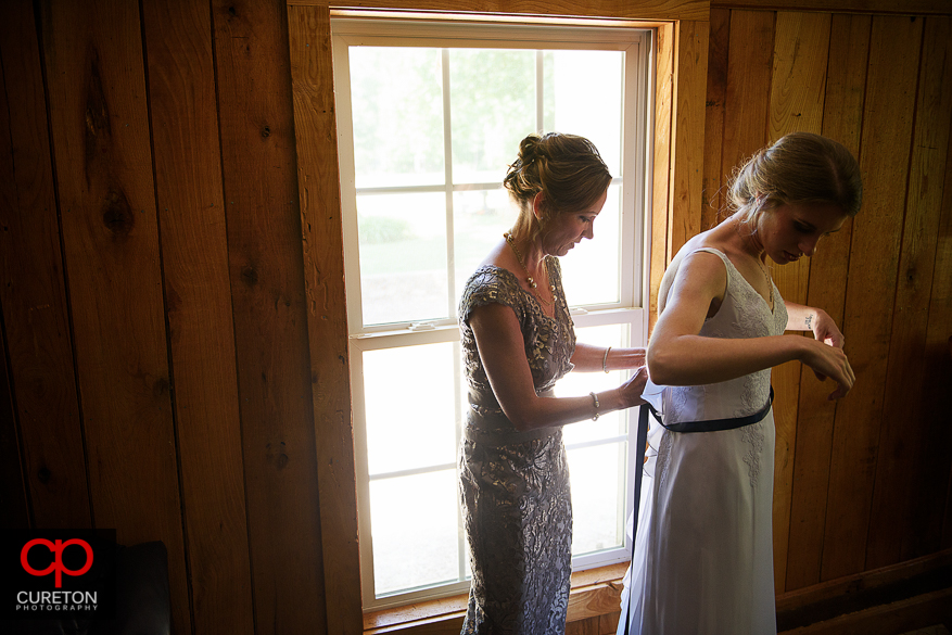 The bride's mom helping her get into the dress.