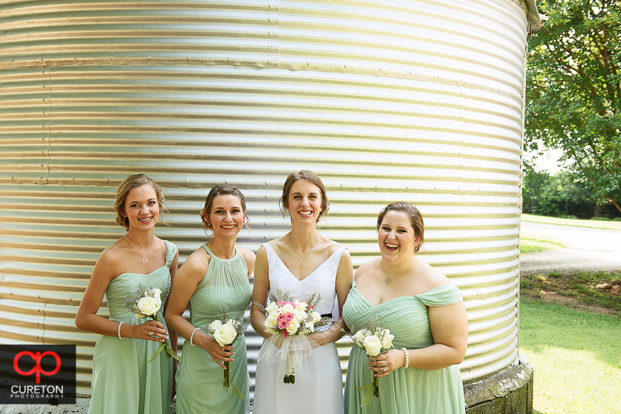 The bride and bridesmaids standing in front of a farm silo.