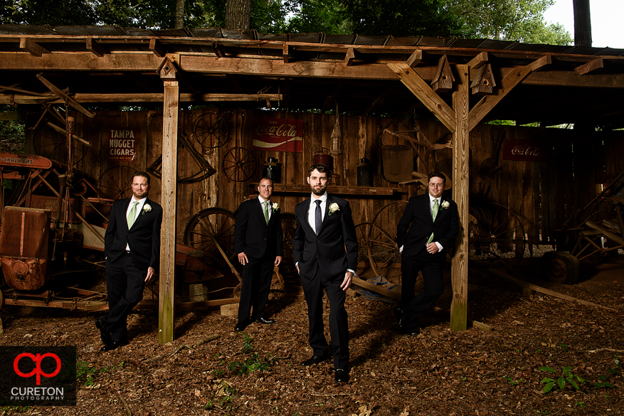 The groom and groomsmen posing with antique farm equipment.