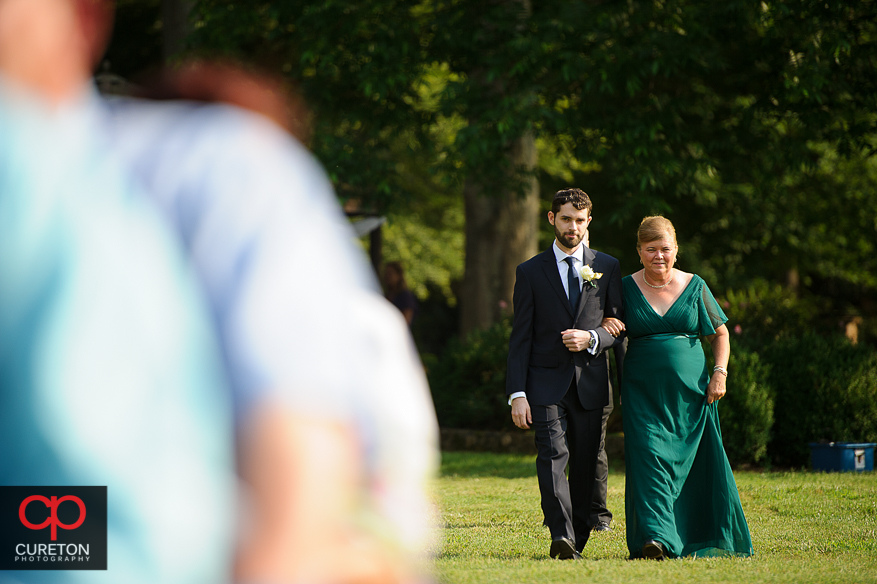 Groom escorts his mother down the aisle.
