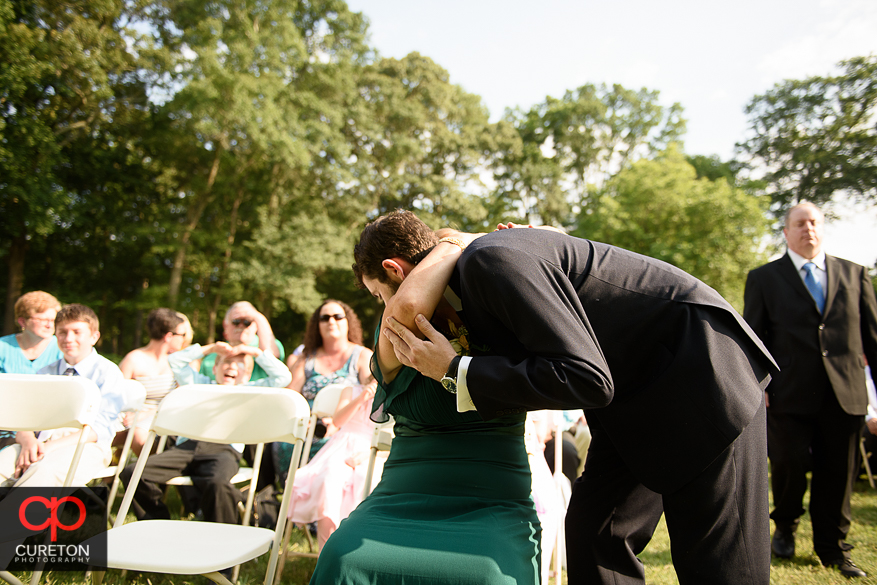 The groom hugs his mother before his wedding.