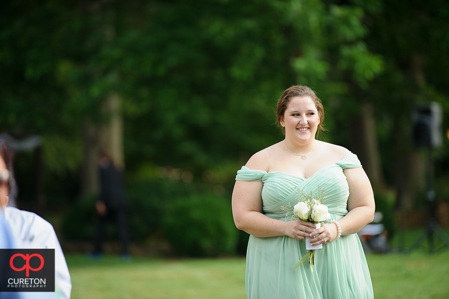 The maid of honor walks down the aisle.