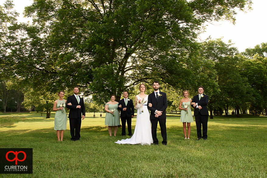The wedding party standing under the tree.