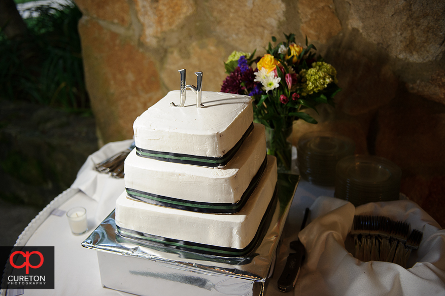 A gorgeous wedding cake with flowers next to it.