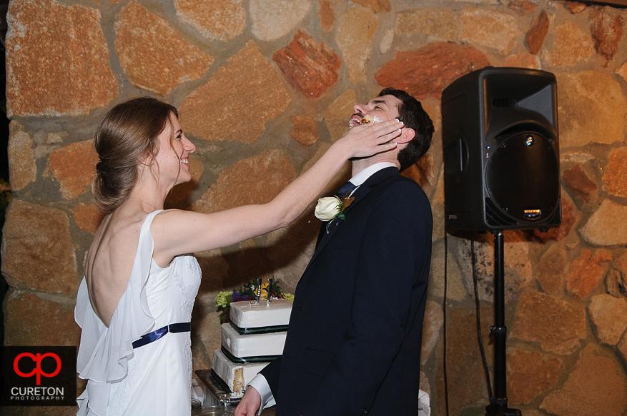 Bride smashing cake on the groom's face.