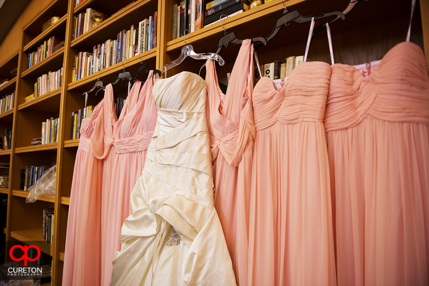 Bride and bridesmaid dresses hanging up together.