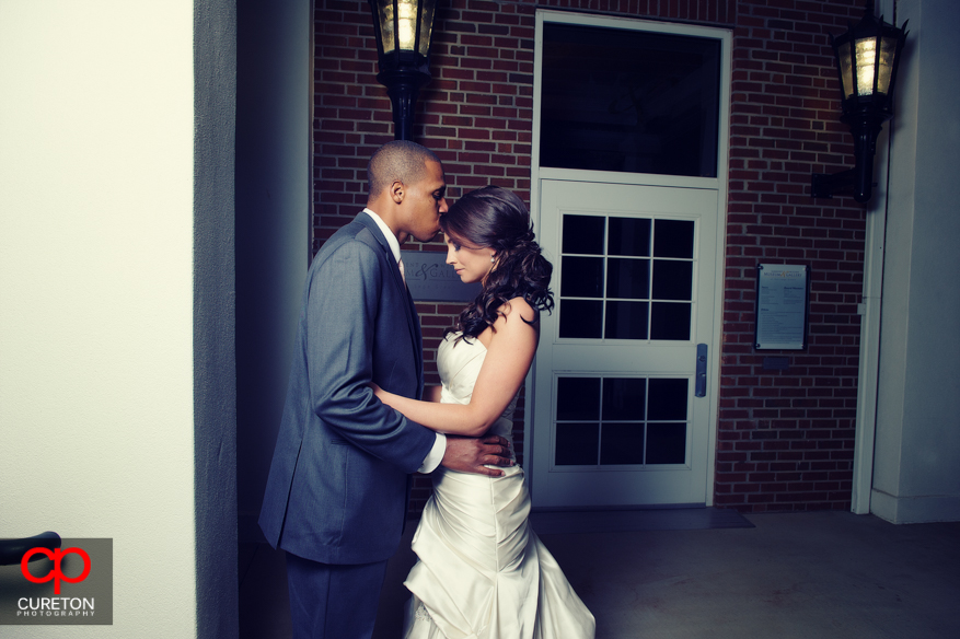 Groom kissing bride on the forehead.