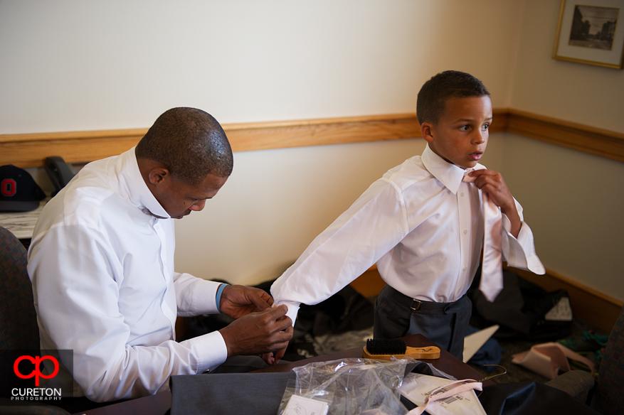 Groom helping son get ready.