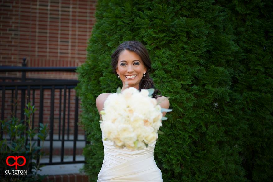 Bride holding bouquet forward.