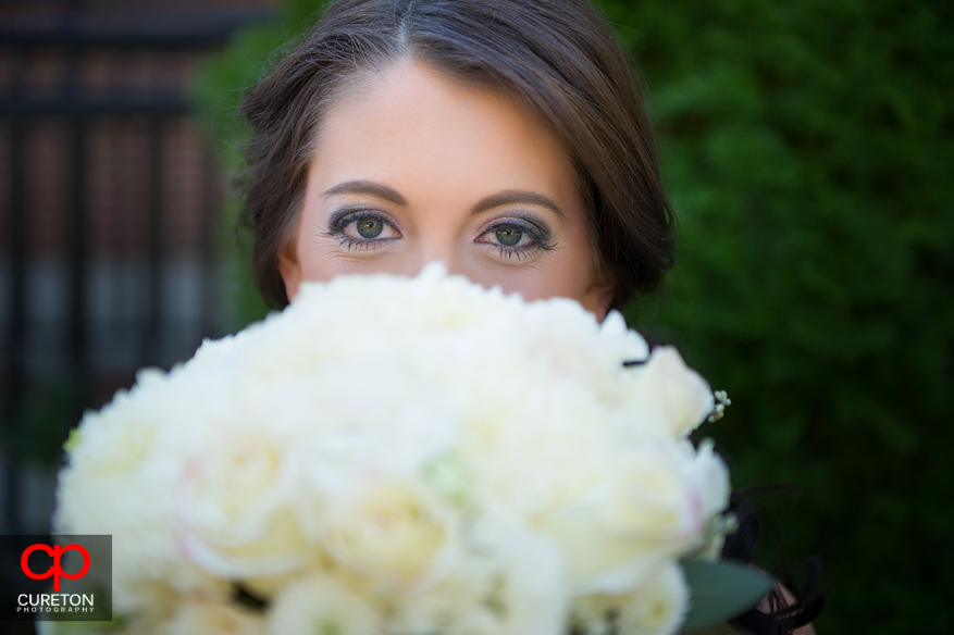 Bride with flowers hiding all but her eyes.