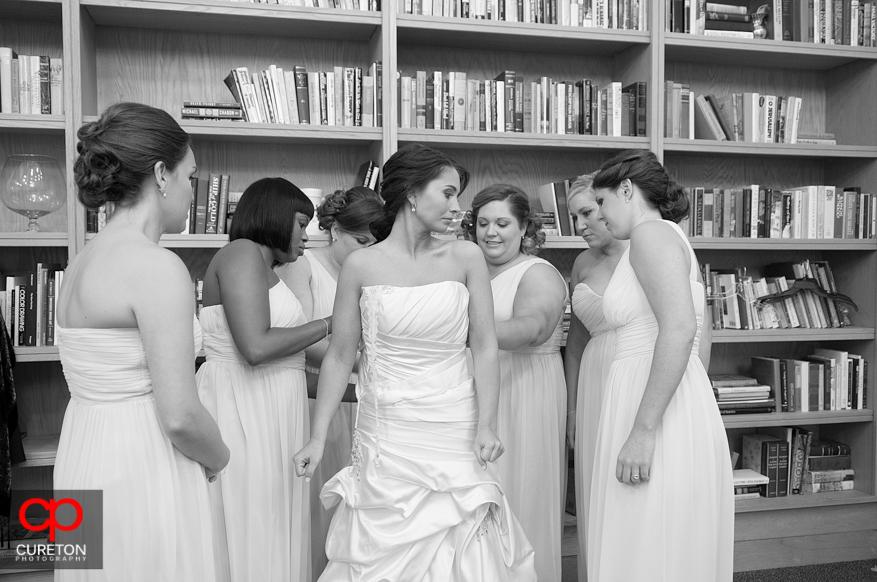 Bridesmaids helping bride into dress.