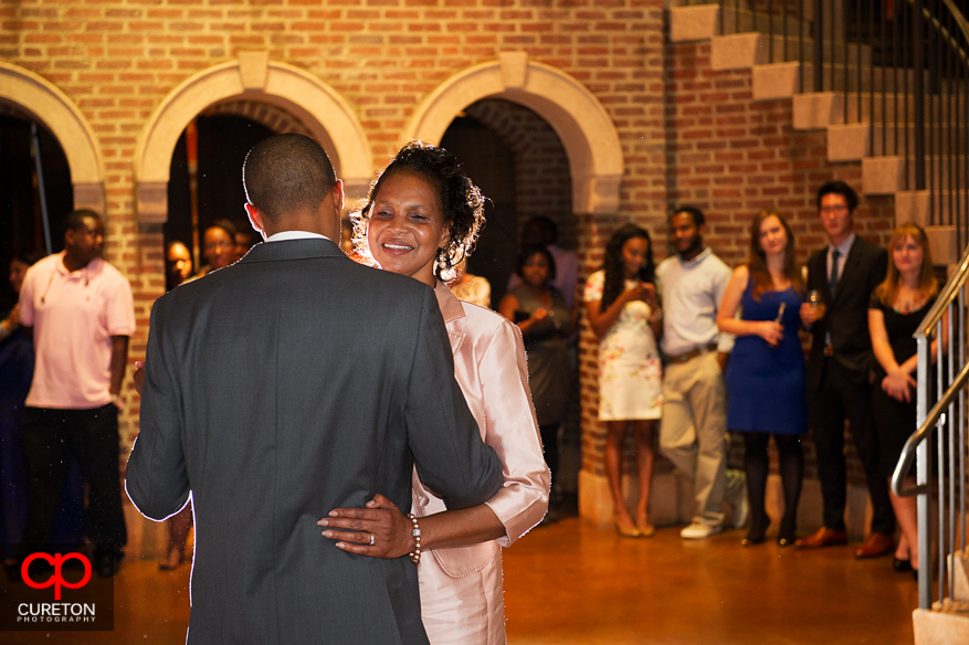 Grooms' mom smiling while dancing with her son.
