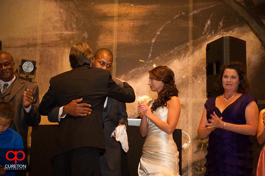 Groom hugging bride's dad.