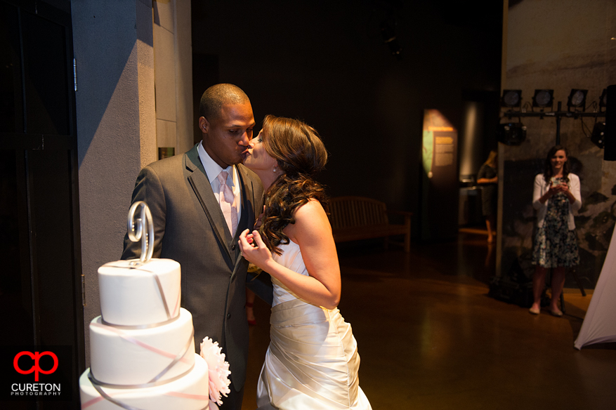 Bride and groom kissing after cutting the cake.
