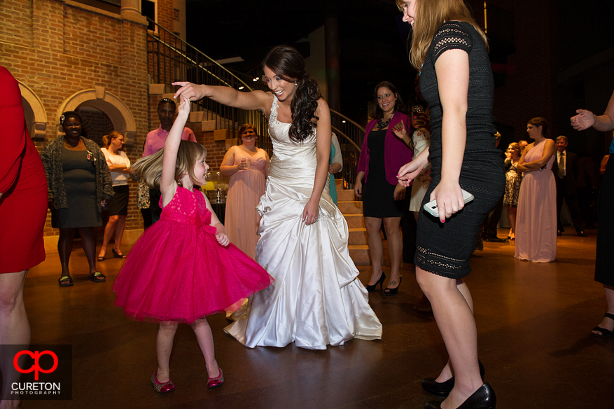 Bride dancing with a little girl.