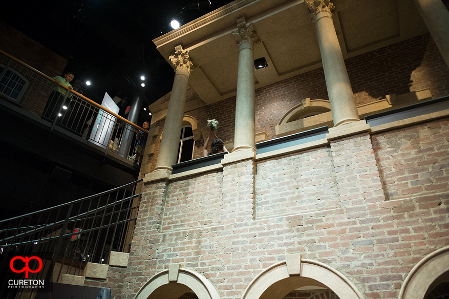Bride throwing the bouquet off the second floor of Upcountry History Museum in Greenville,SC.
