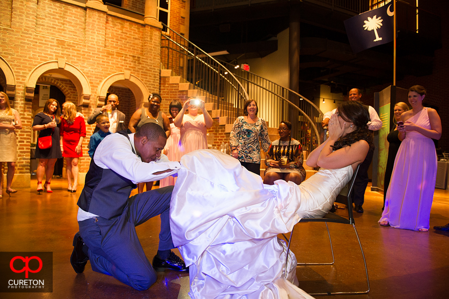 Groom taking off the bride's garter.