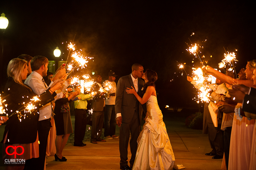 Couple kissing in a sea of sparklers outside Upcountry History Museum after their wedding reception.