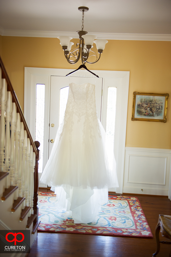 Bride's dress hanging up in the foyer.