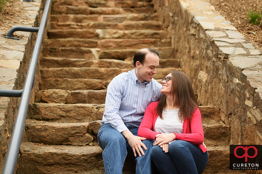Couple sitting on the steps in Falls Park during an engagement session.