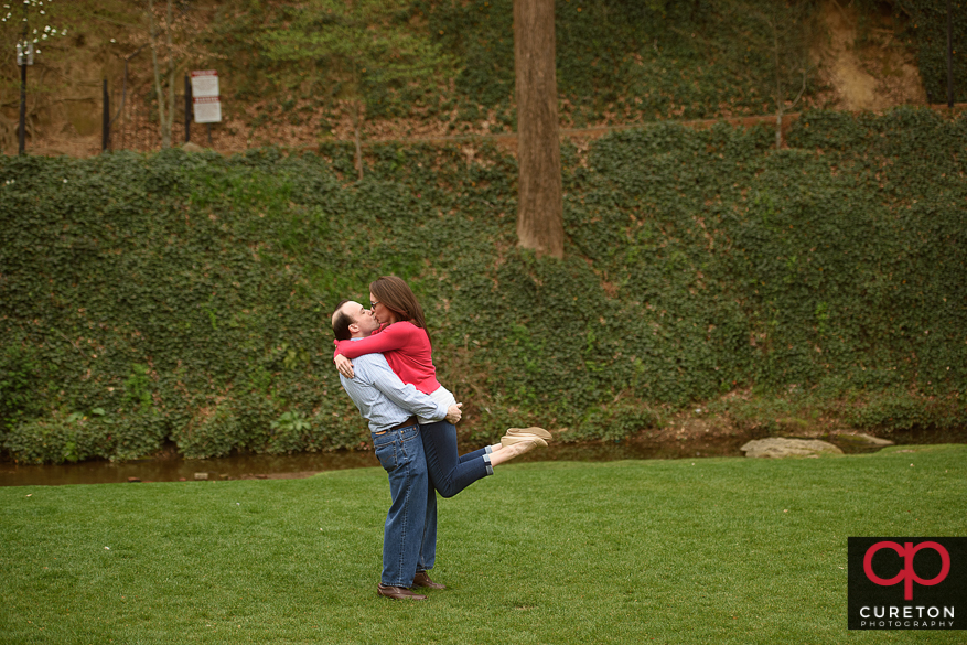 Man lifting his fiancee during a sessionin downtown Greenville,SC.