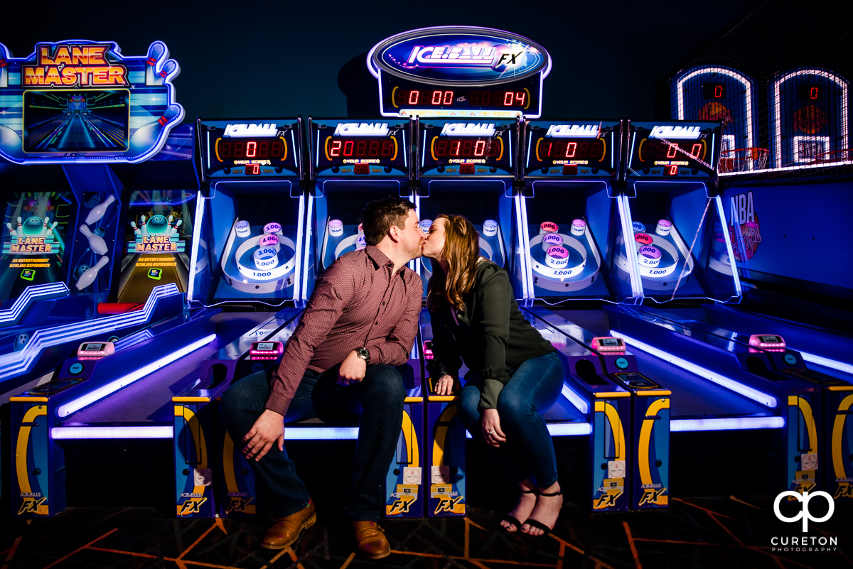 Engaged couple kissing on a skee ball machine at their arcade engagement session at Spare Time in Greenville,SC.