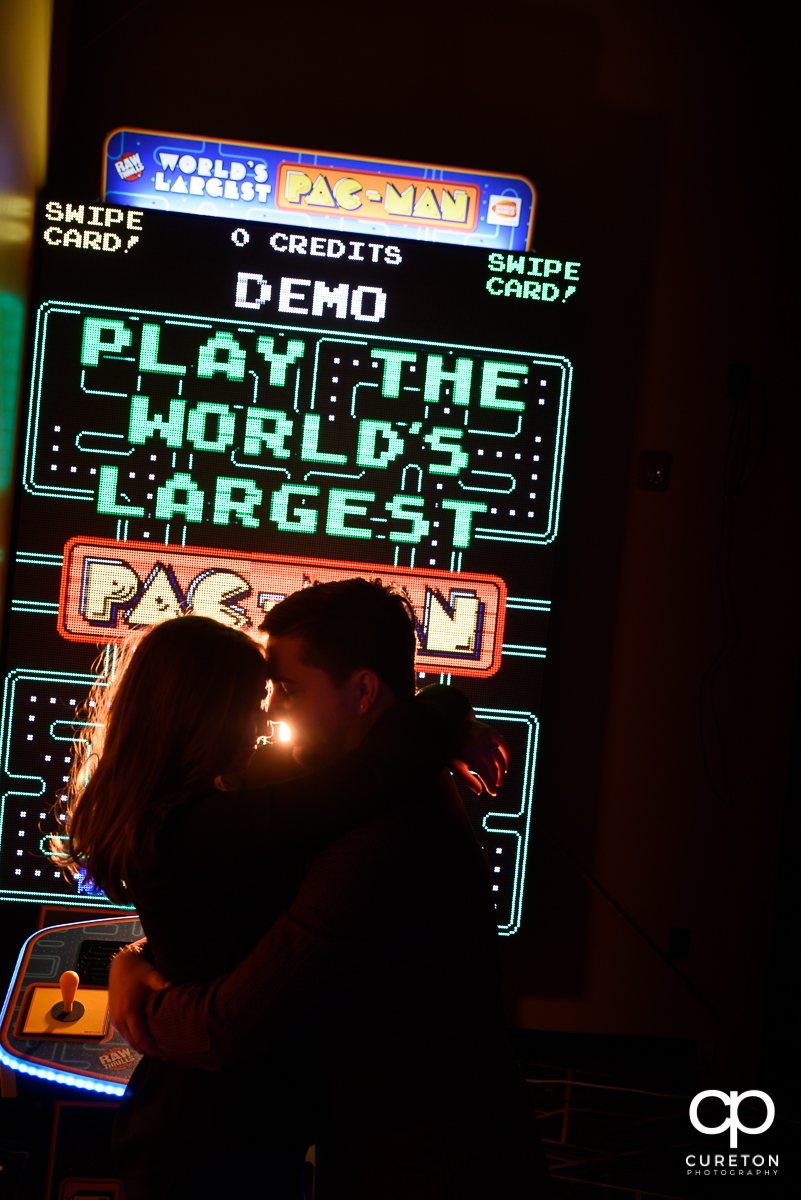 Engaged couple dancing in front of a Galaga machine at their arcade engagement session at Spare Time in Greenville,SC.