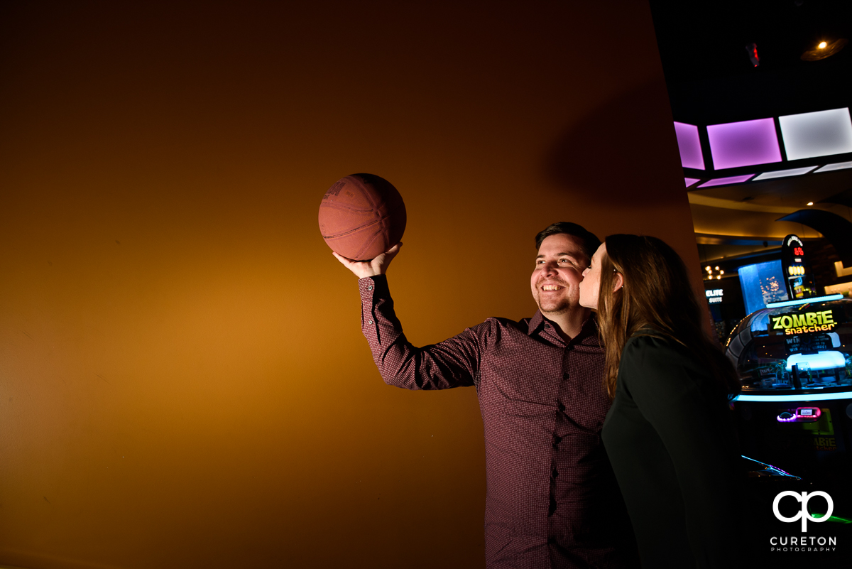 Future bride kissing her groom on the cheek as he shoot a basketball inside a fun park.