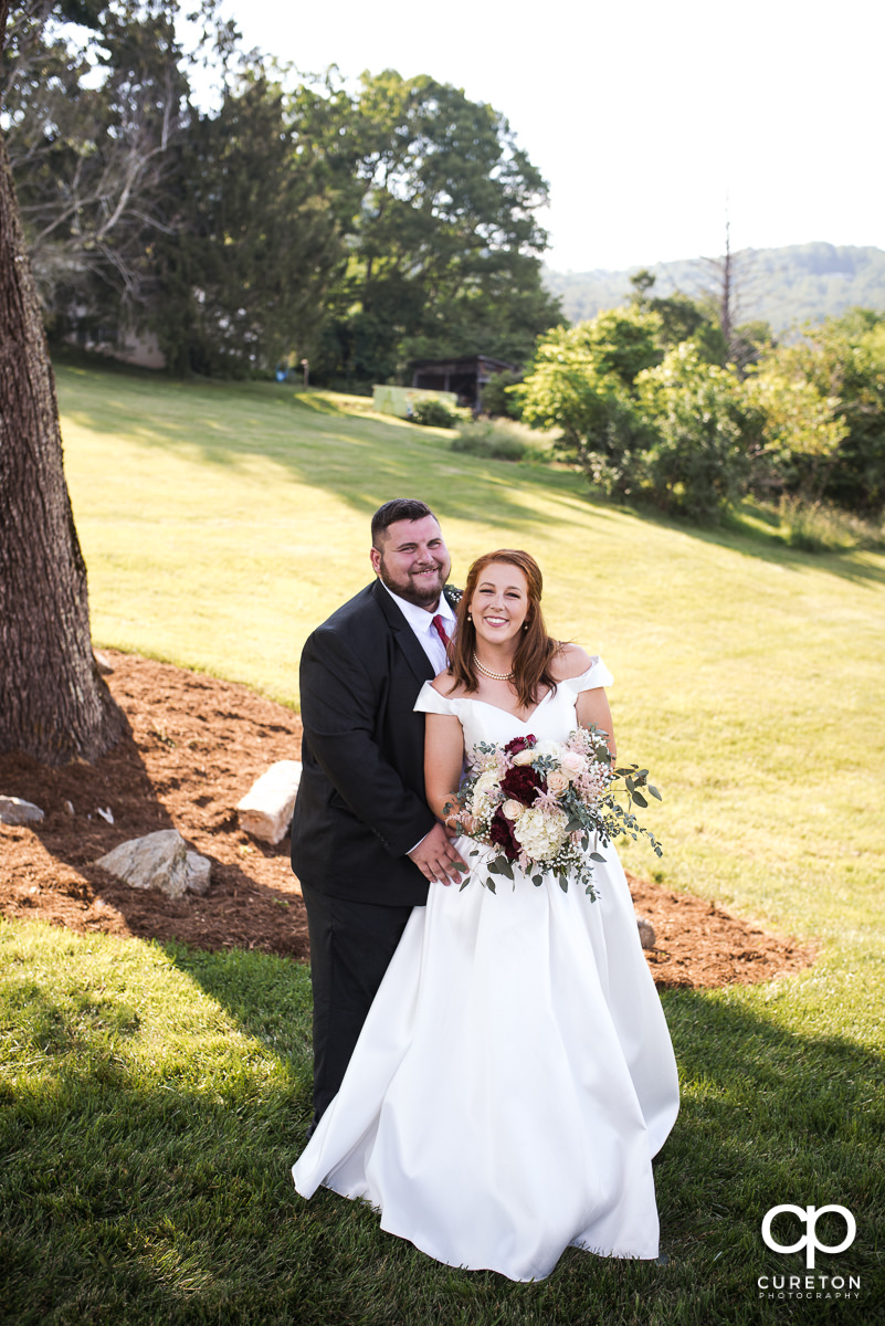 Bride and groom snuggling after their Asheville NC outdoor wedding ceremony.