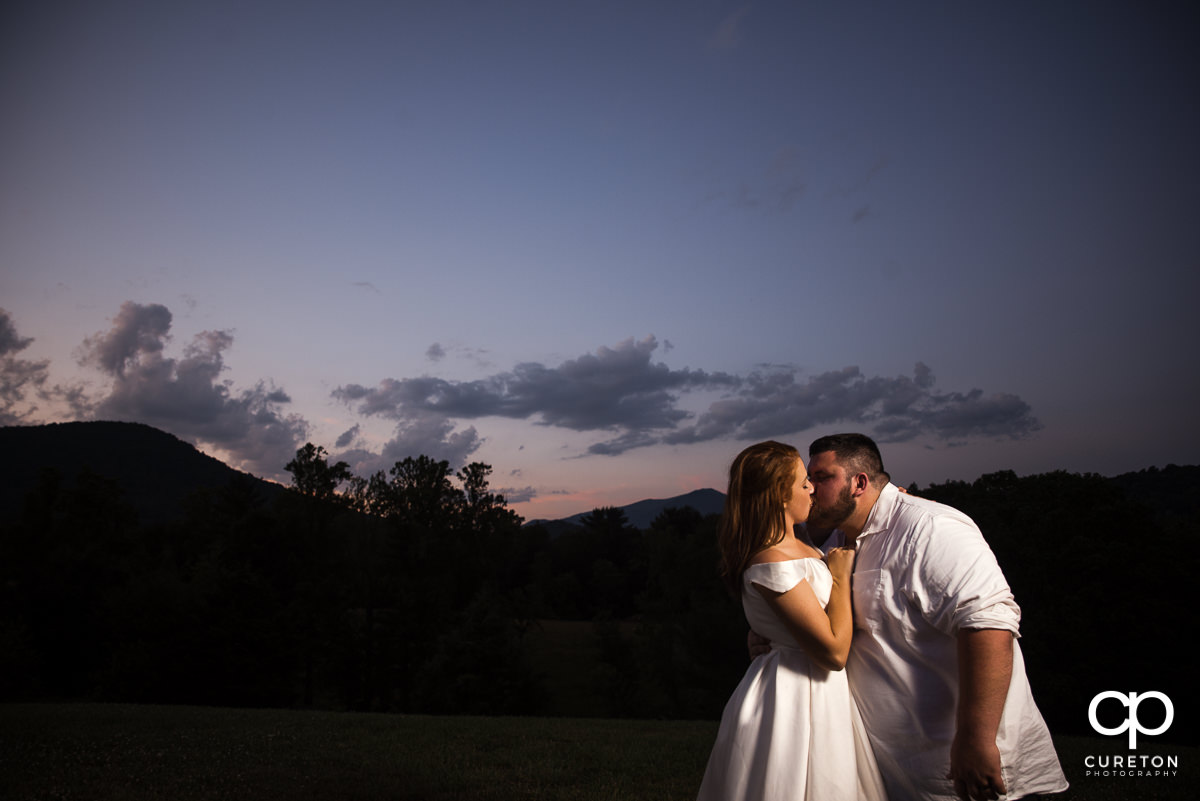 Groom kissing his bride underneath a sunset sky and mountain backdrop after their Asheville NC outdoor wedding.