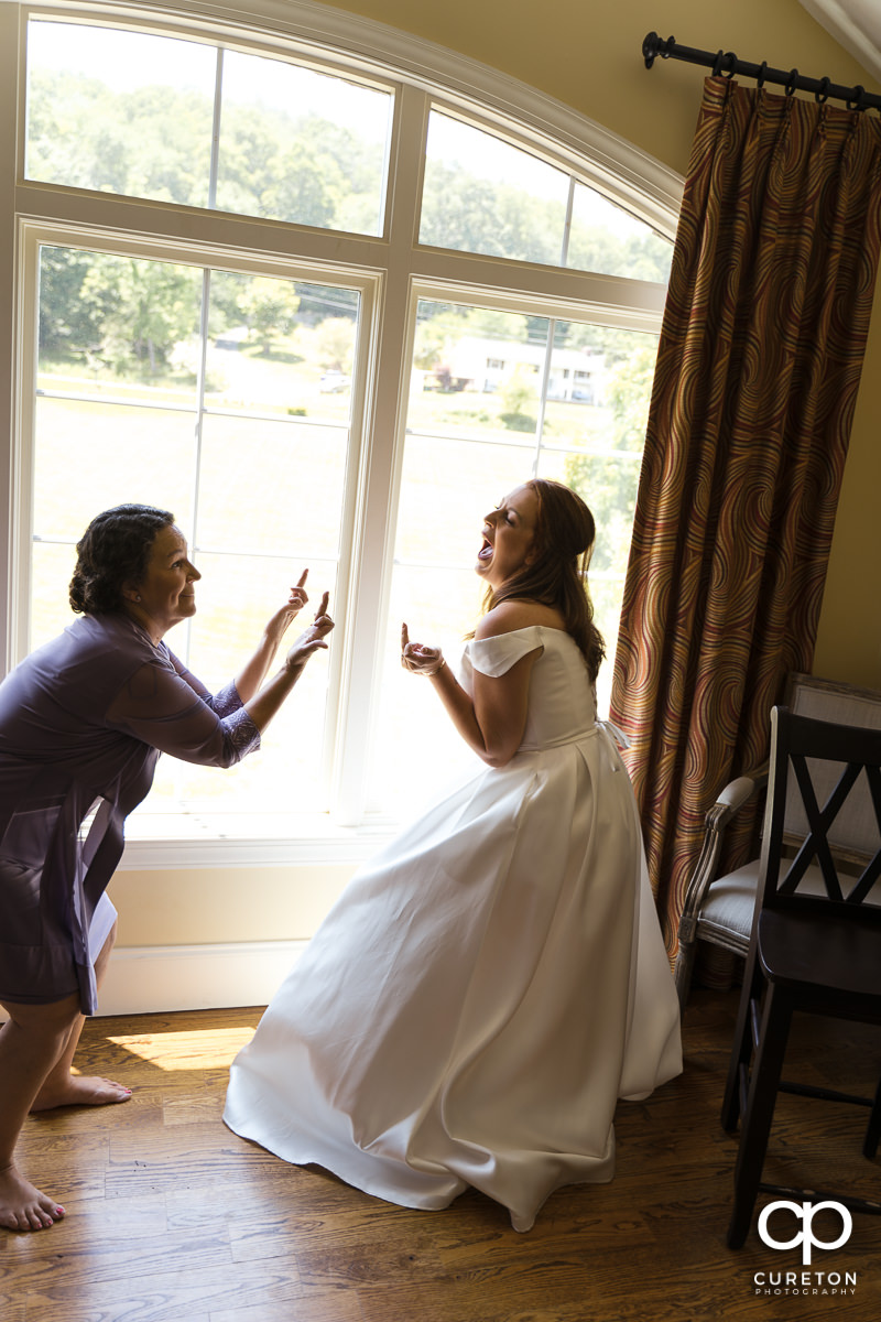 Bride and her mom giving each other the finger.