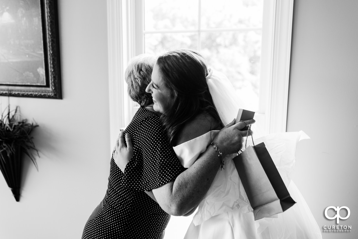 Bride hugging her mother in law.
